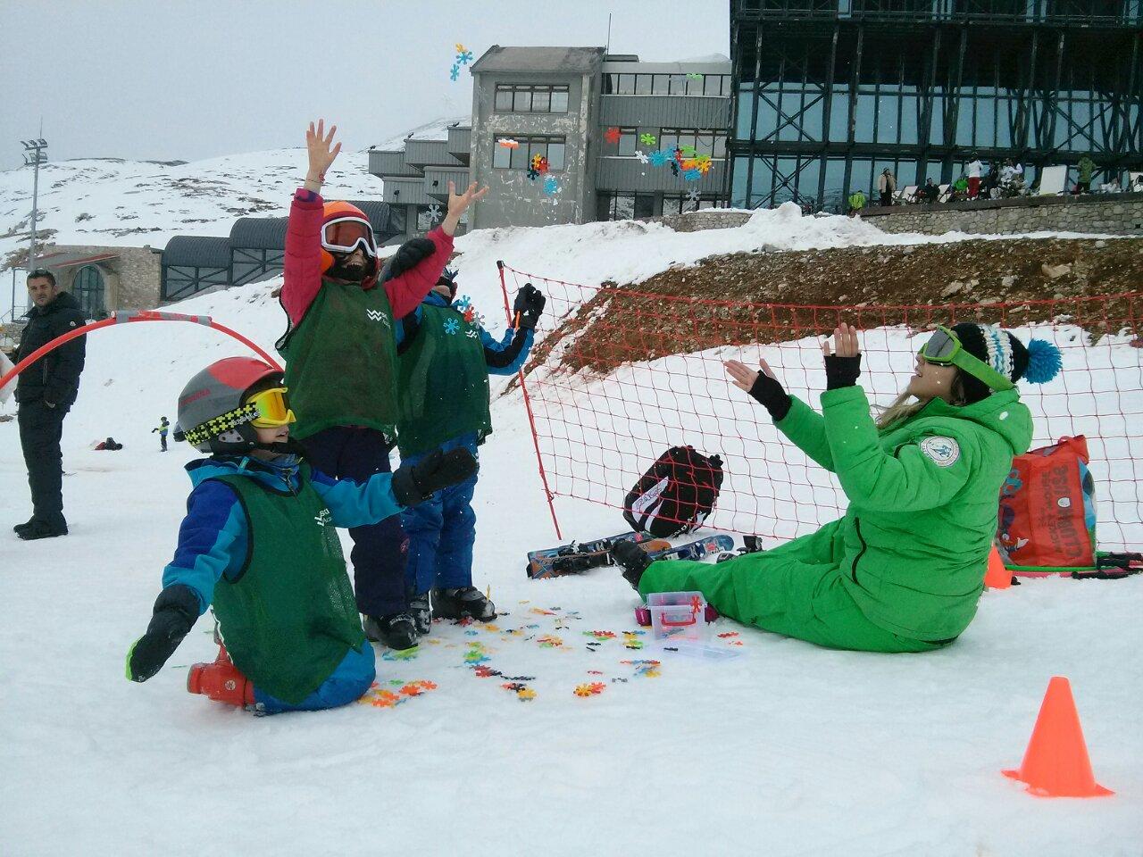 Η εκπαιδεύτρια σκι διασκεδάζει στο βουνό τρεις μικρούς σκιερ με