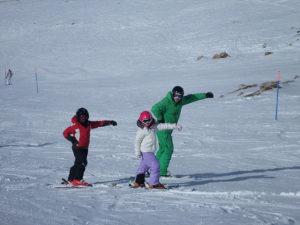 Η προπονήτρια σκι δείχνει στους μικρούς μας φίλουν πως να γλυστρούν με τα πέδιλα του σκι